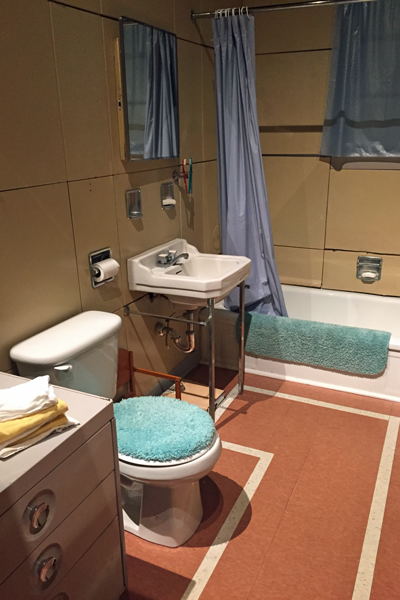 The bathroom. Notice how the wall panels curve at the bottom over the tub for a drip edge.