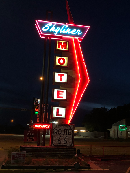 The Skyliner Motel sign at night.