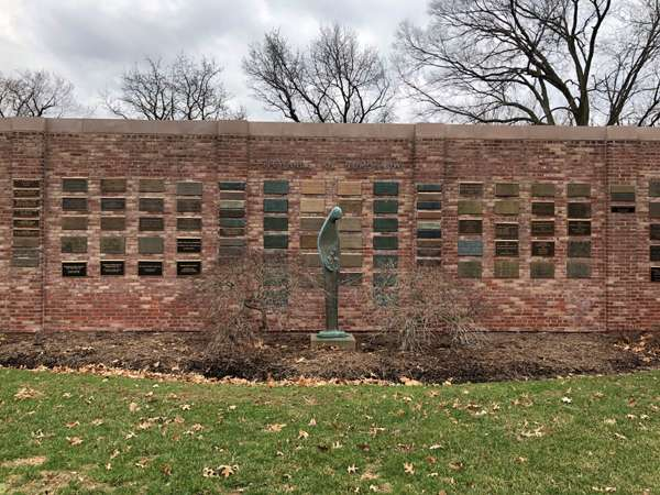 Brick privacy wall with plaques and sculpture.